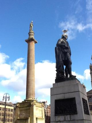 Robbie Burns (foreground) and Sir Walter Scott (background), both wearing seagulls as hats. High style for statues in George Square, Glasgow.